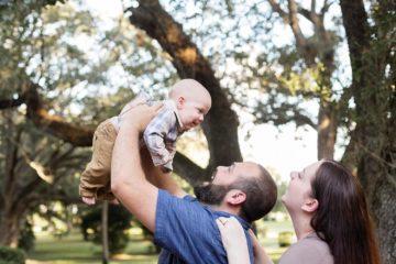 daddy holding baby in the air smiling