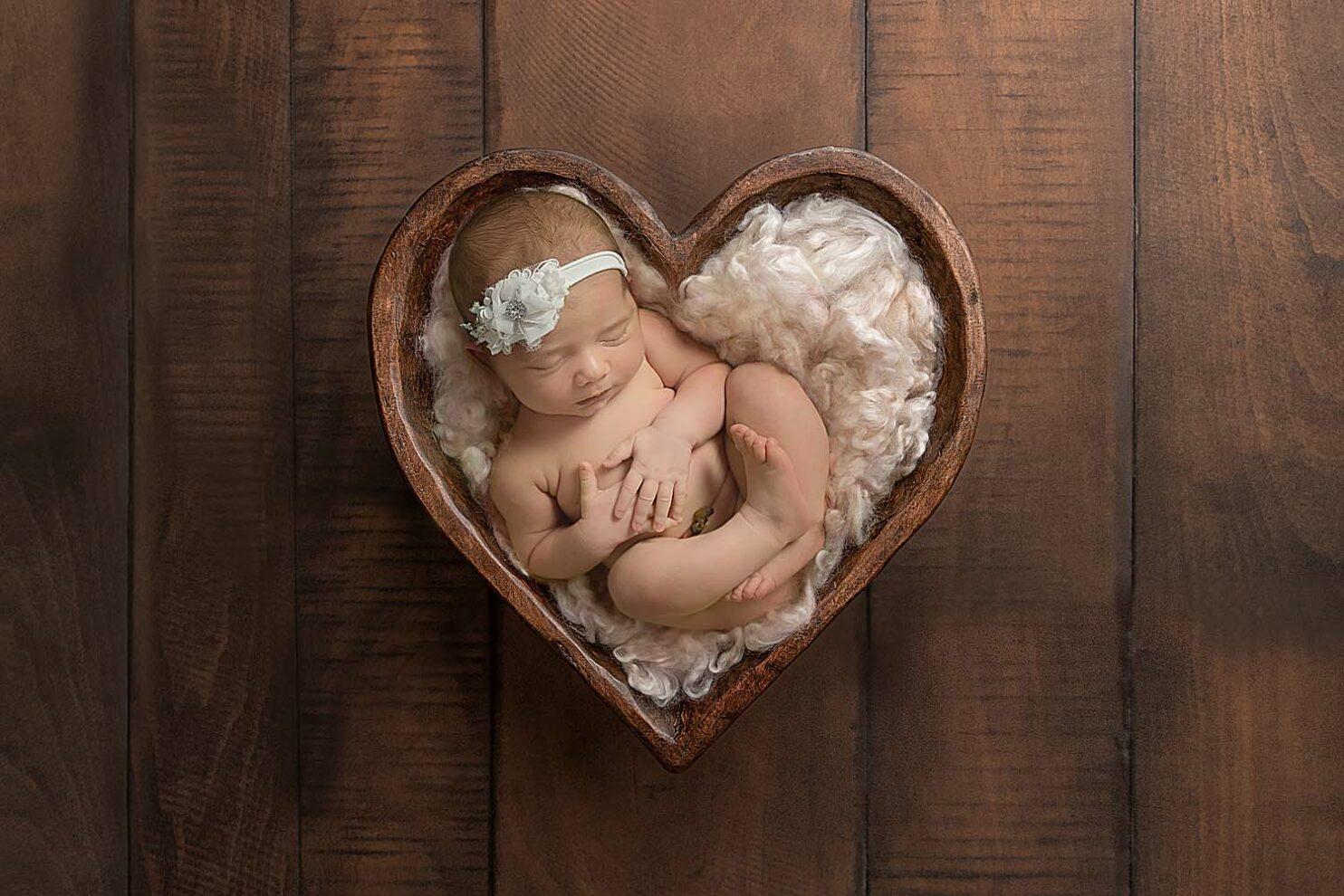 newborn baby in wood heart