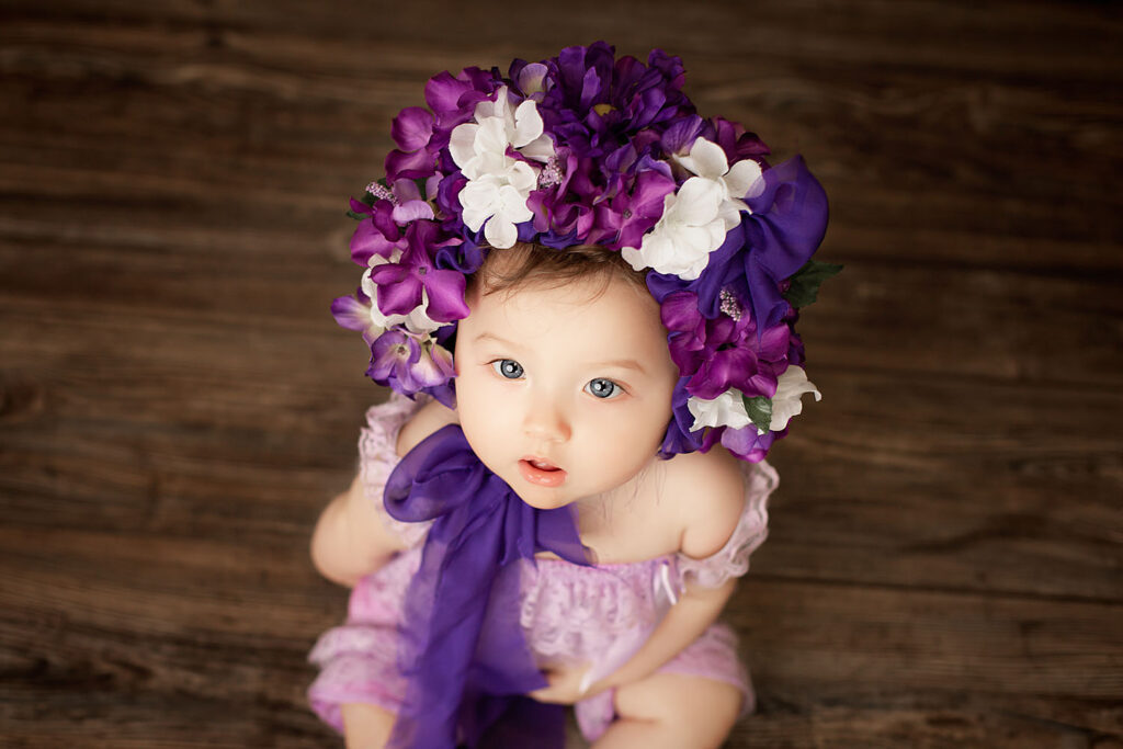 baby girl wearing purple flower bonnet for milestone photos in south florida