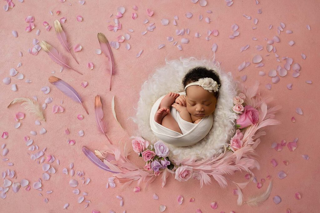 newborn baby girl photographed on flower prop in coral springs, fl