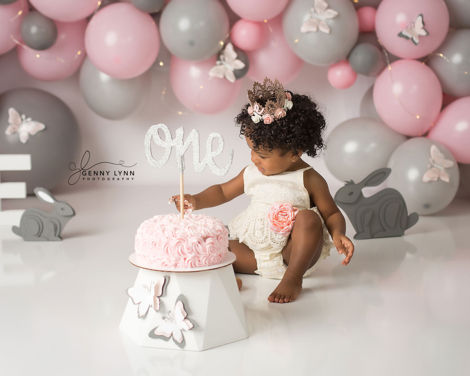 one year old girl sitting and eating cake at her cake smash session in south florida