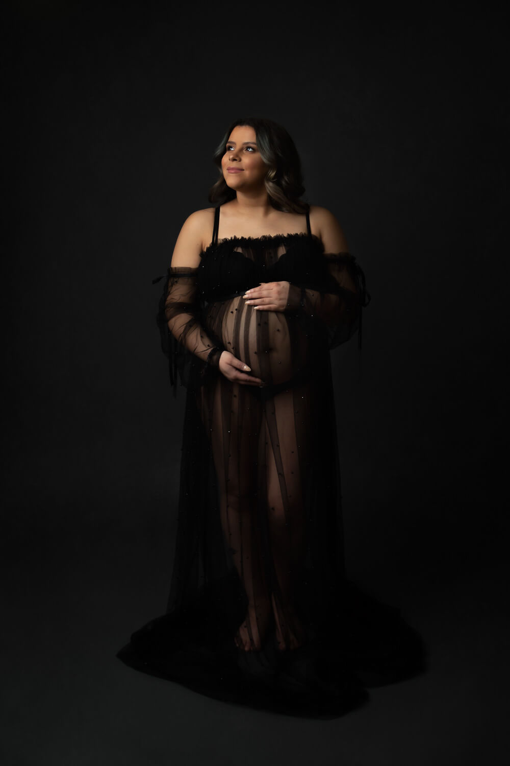 pregnant woman posing for maternity photo in gown