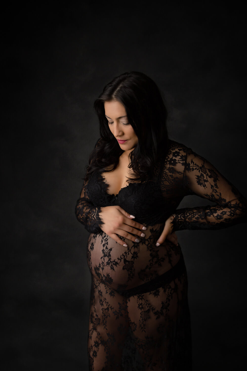 pregnant woman posing for maternity photo in black lace gown looking at her belly