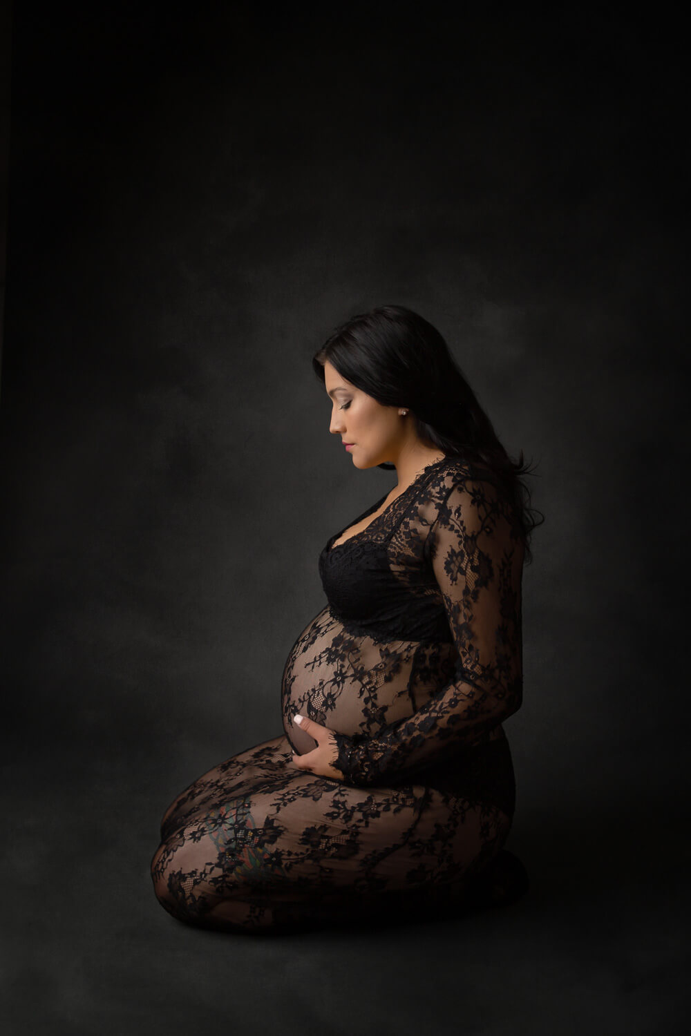 pregnant woman posing for maternity photo in black lace gown kneeling