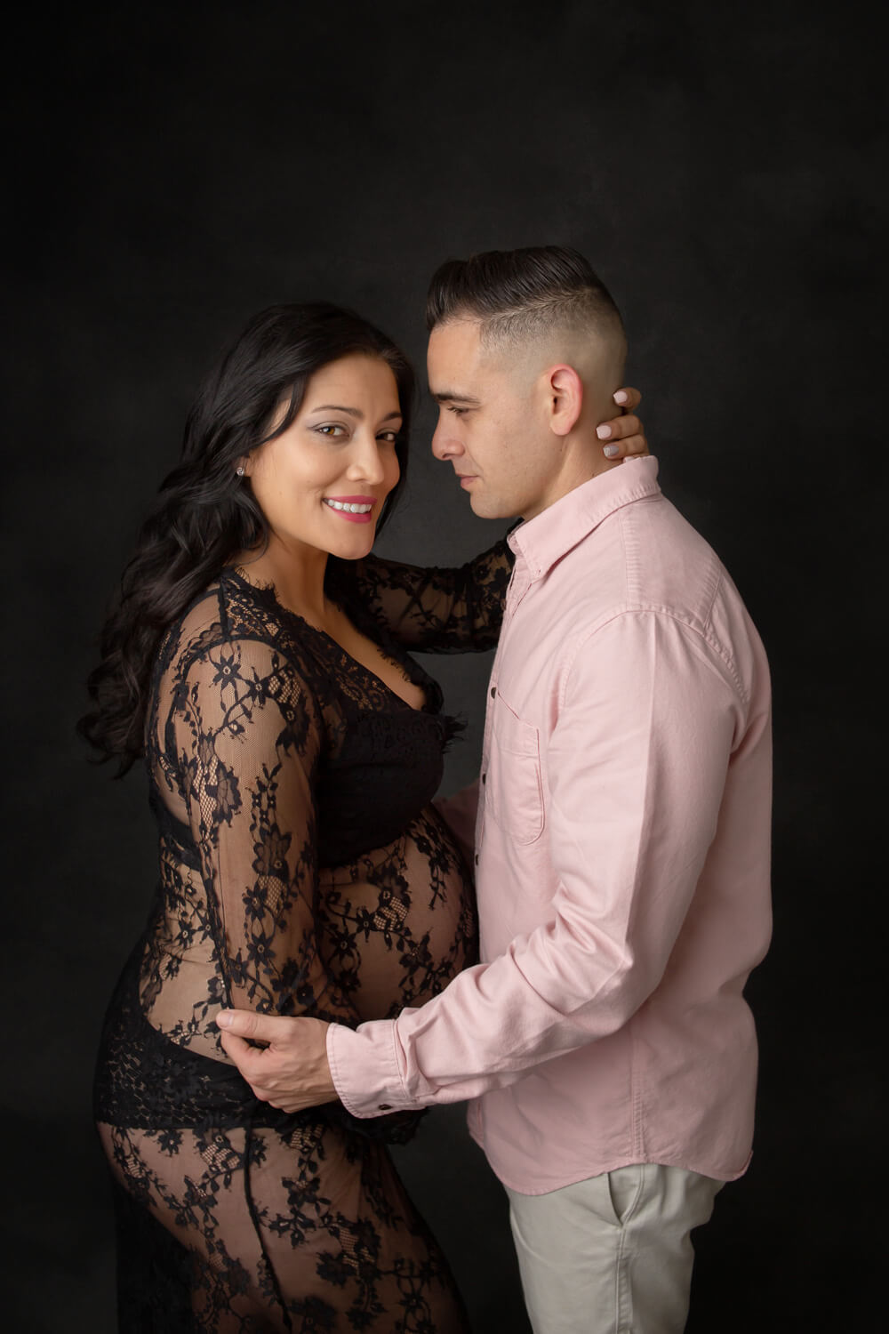 pregnant woman posing for maternity photo in black gown with her man