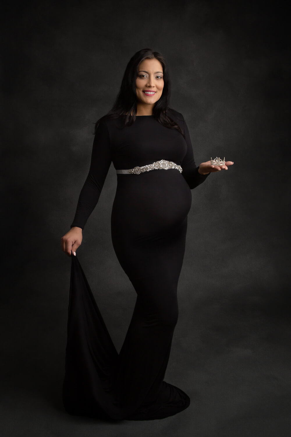 pregnant woman posing for maternity photo in black gown holding tiara