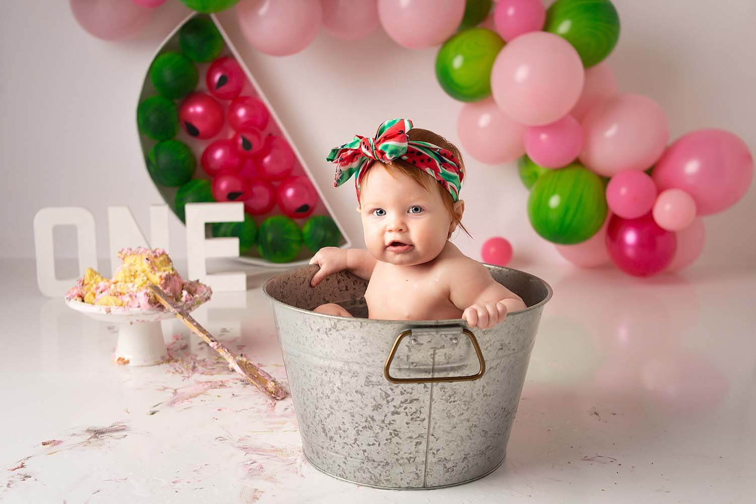 one year baby watermelon cake smash photoshoot in bucket with feet out
